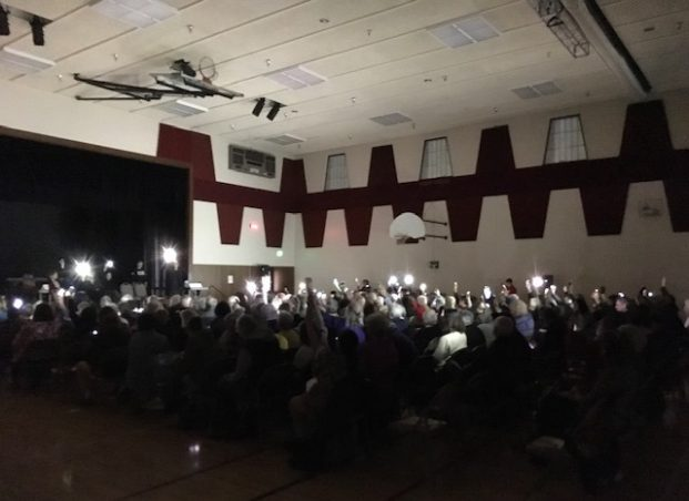 An audience shows its support for detained immigrants after a March 28, 2019 performance in Puyallup, Washington, holding lights aloft for a moment of silence.